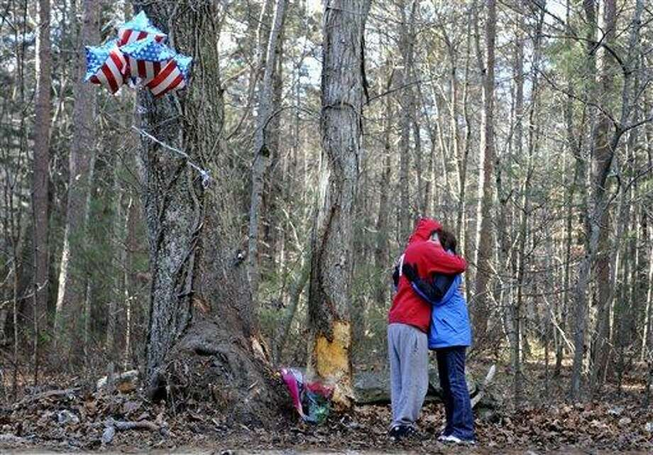 Friend of victims, Bryan Plecan, left, embraces Laura Marsh, of Griswold, a mother who lost her teenage son in an accident four months earlier, at the scene of the crash where four teens were killed in a single-vehicle accident in Griswold, Conn., Wednesday, Dec. 8, 2010.  (AP Photo/Jessica Hill) Photo: AP / AP2010