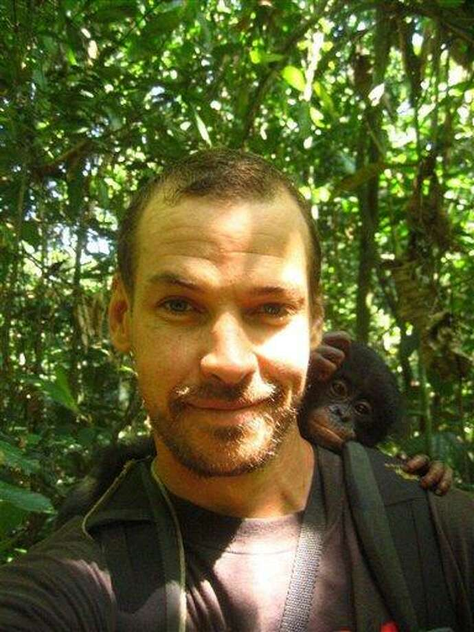 This undated photo supplied by Fluidkayaks shows South African Kayaker, Hendri Coetzee, posing with a monkey on his shoulder. Coetzee, who was leading two Americans on a whitewater expedition in Central Africa is presumed dead after a crocodile attacked the kayak and dragged him away, rescuers said Thursday, Dec 9, 2010. (AP Photo-Fluid Kayaks-HO) Photo: AP / AP