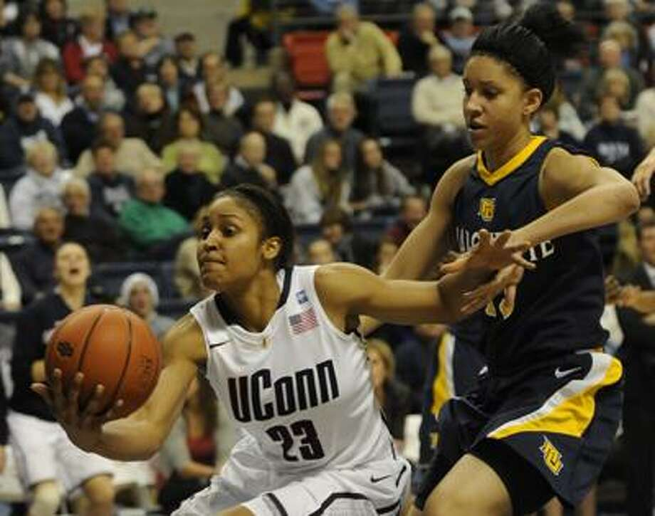 Connecticut's Maya Moore (23) pulls in a loose ball past Marquette's Courtney Thomas in the second half of an NCAA college women's basketball game at Storrs, Conn., Thursday, Dec. 9, 2010. (AP Photo/Bob Child) Photo: AP / FRE 170410 AP