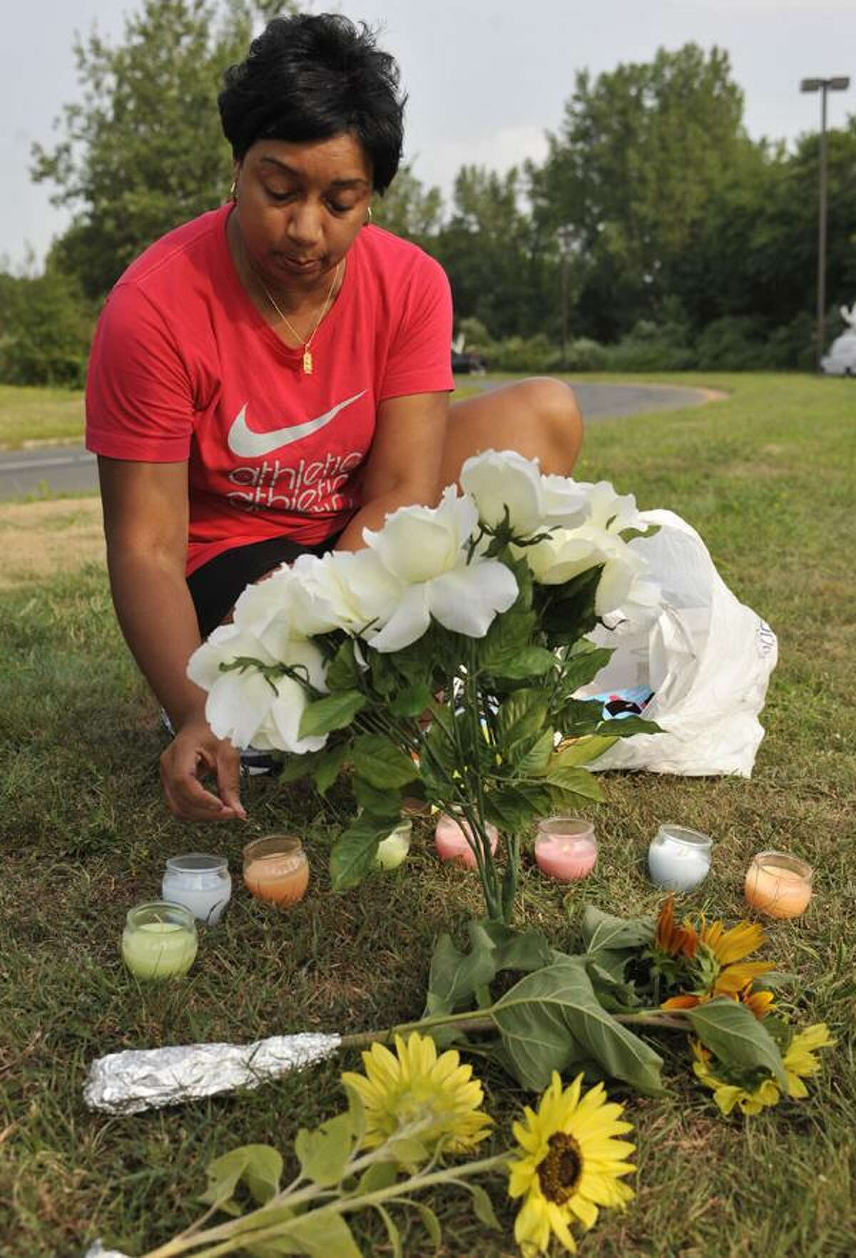 Terrie Thomas, of South Windsor, lights a candle for each victim killed outside of Hartford Distributors in Manchester, Conn., Wednesday, Aug. 4, 2010. Omar S. Thornton, a driver for Hartford Distributors, killed eight people, plus himself at the beer distribution company in Connecticut on Tuesday morning. (AP Photo/Jessica Hill)