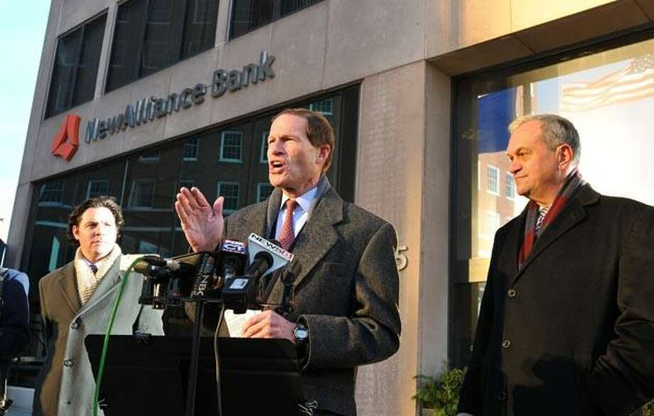 Attorney General/Senator elect Richard Blumenthal calls for hearings and scrutiny on the proposed merger with NewAlliance Bank and First Niagara. Behind him on right is New Haven Mayor John DeStefano, who also spoke strongly on the issue and on left is Louis Mangini, a spokesman for Congresswoman Rosa DeLauro. The press conference was held in front of the NewAlliance Bank on Church Street. (Photo by Peter Casolino/New Haven Register)