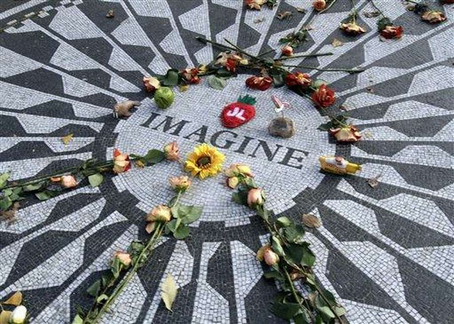The Imagine mosaic in Strawberry Fields is decorated with flowers and other mementos,  Tuesday, Dec. 7, 2010 in New York. Wednesday marks 30 years since John Lennon was murdered outside his New York apartment, triggering a wave of grief around the world. (AP Photo/Mary Altaffer) Photo: ASSOCIATED PRESS / AP2010