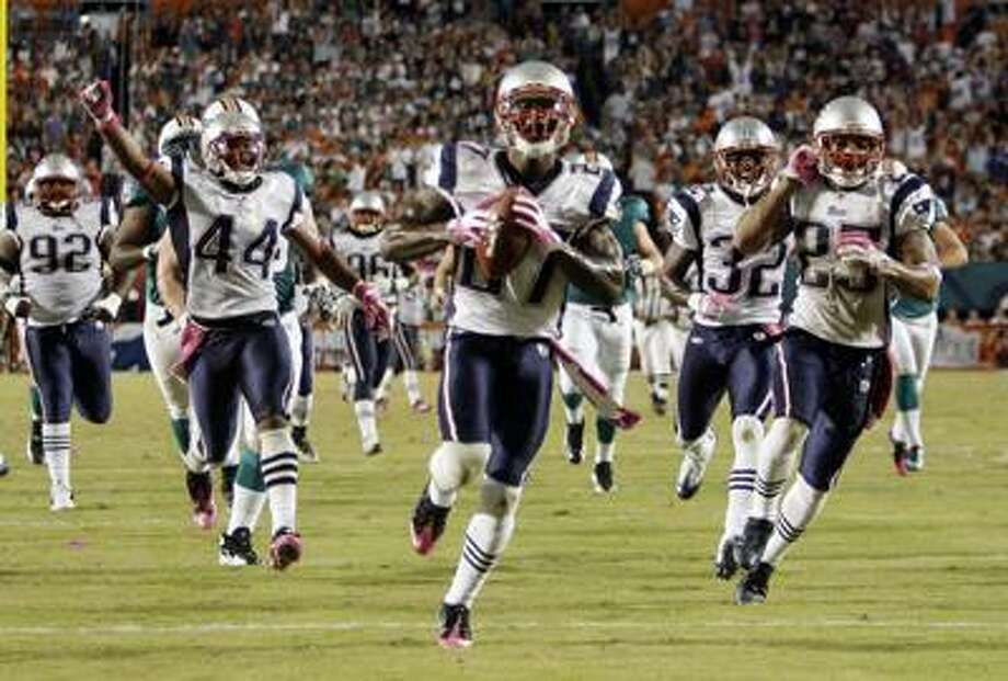 The Patriots' Kyle Arrington runs toward the end zone after he recovered a blocked Dolphins field goal during the second half of New England's 41-14 win Monday night in Miami. (Associated Press/Lynne Sladky) Photo: AP / AP