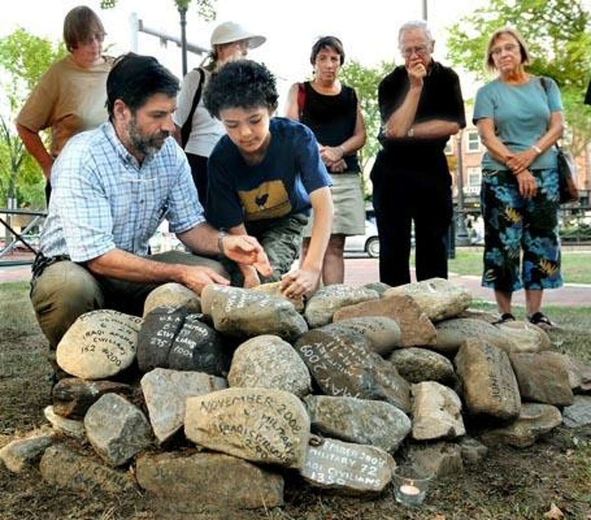 On the Green between Elm Street and Broadway, Ray Pagliaro (L) and his son Edwardo Pagliaro-Haque, 8, of Hamden, place a stone on a cairn marking the dead fin Afghanistan and Iraq. A new stone marking the dead is ceremoniously placed each month. (Melanie Stengel/Register)