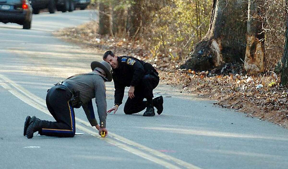 Connecticut State Trooper James Collins, left, and Officer Mark Pereira of the Accident Reconstruction Squad, take measurements Wednesday, Dec. 8, 2010, in Griswold, Conn., at the scene where four Griswold High School students were killed and one critically injured after a teen driver lost control on Tuesday, and crashed into the tree seen at right. (AP Photo/Norwich Bulletin, John Shishmanian)