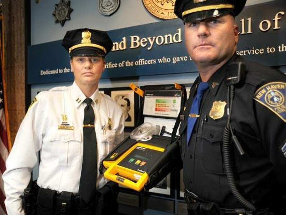 New Haven police Capt. Joann Peterson, left, and Sgt. John Magoveny with the defibrillator they used to save a stricken man at police headquarters. (VM Williams/Register)