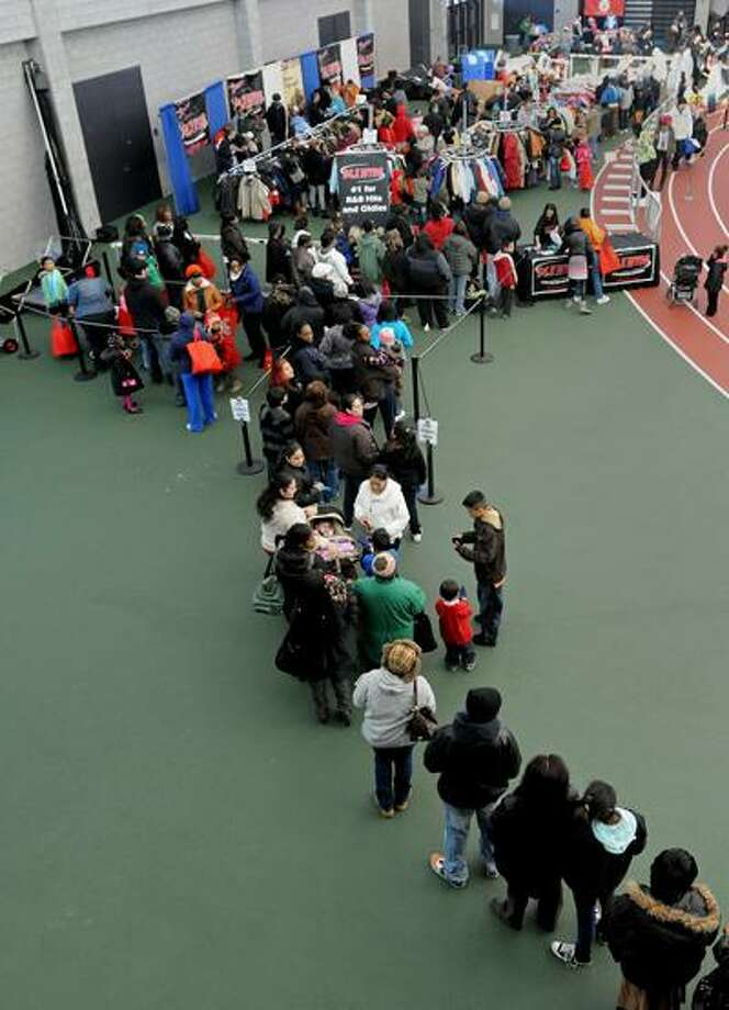 New Haven--A line of hundreds of New Haven community members extends from the out in the hallway into the New Haven fieldhouse at Sunday's winter coat distribution.  Photo by Brad Horrigan/New Haven Register-12/05/10.