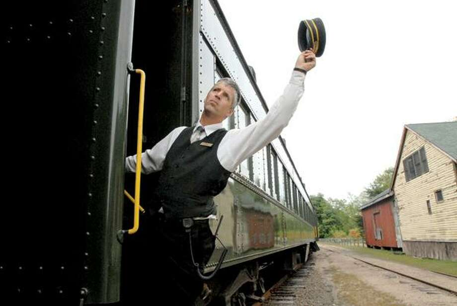 Rob Bradway, conductor and defacto maitre d' of the Valley Railroad's Essex Clipper Dinner Train ride, signals that the train can start its journey along the shoreline. The train mimics the romance, intimacy and adventure of fine dining in a 1920s-style Pullman dinner train car.