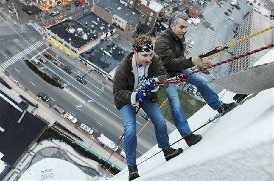 New York Yankees general manager Brian Cashman, left,  scales down the outside of the 22-story Landmark Building in Stamford, Conn., Friday, Dec. 3, 2010.  Cashman was strapped into a cable for the practice run before a holiday show on Sunday. At right is climber Brian Van Orsdel.  (AP Photo/The Advocate, Kathleen O'Rourke) Photo: AP / Stamford Advocate