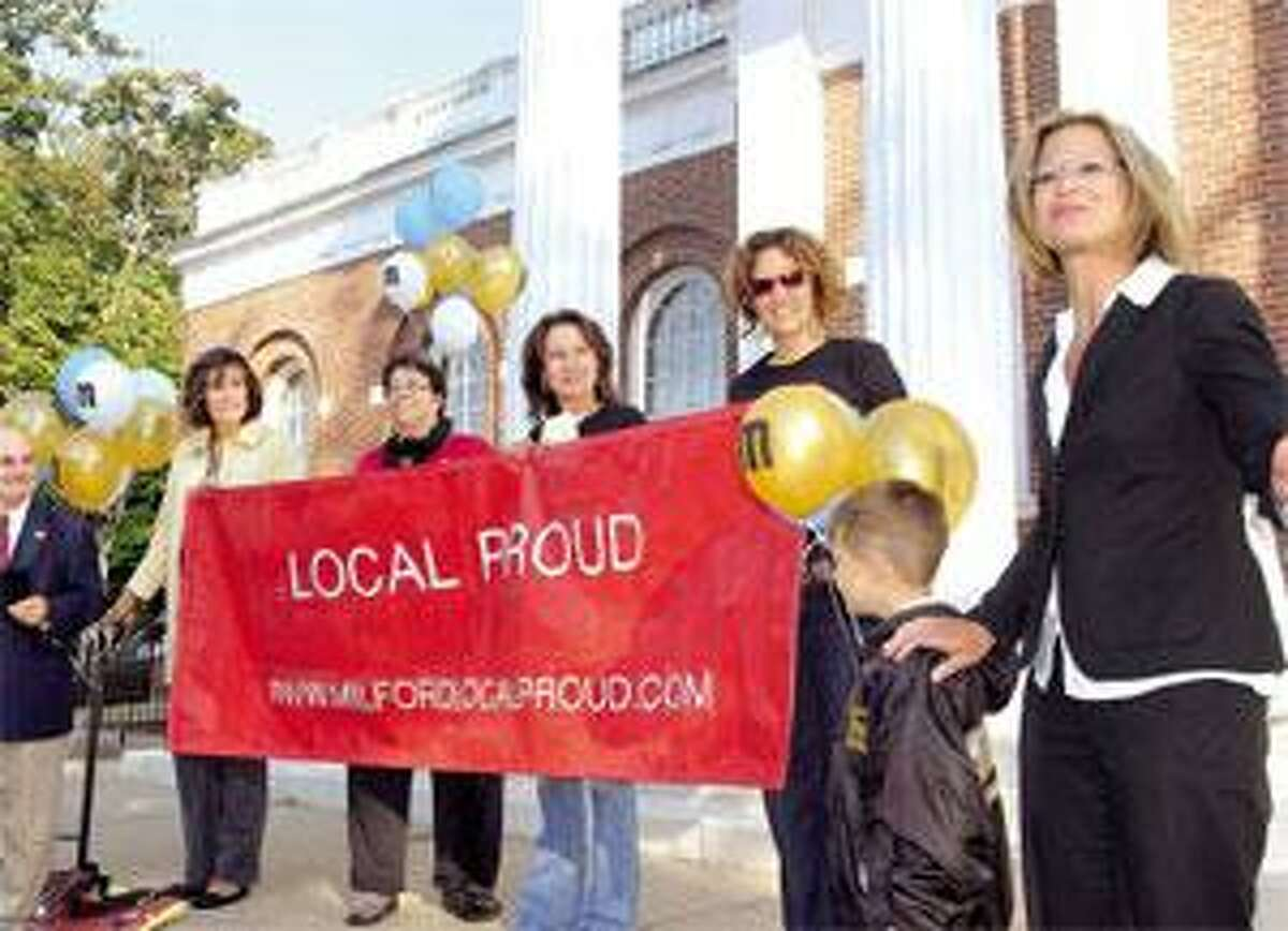 """Promoting """"Local Proud"""" week on the steps of Milford City Hall are, from left, Milford Mayor James L. Richetelli Jr., Economic Development Commisioners Susan Patrick, Tessa Marquis and Susan Ashelford, business owner Dayan Moore, Geno Salvatore and EDC Chairwoman Genevieve Salvatore. (Melanie Stengel/Register)"""