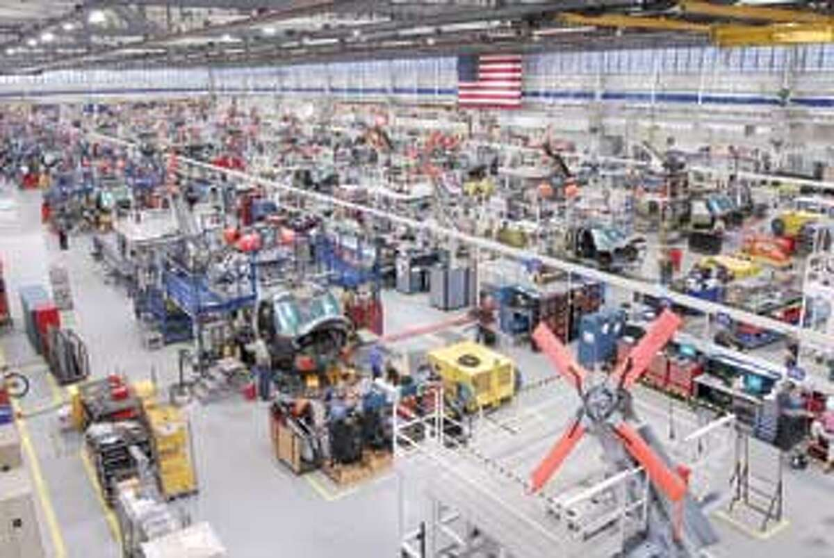 Work is done on UH-60 series helicopters at one of Sikorsky Aircraft Corp.'s assembly lines in Stratford. Businesses like Sikorskey that have federal government contracts soon will have to use a government-run online system to verity the eligibility of all workers assigned to the contracts. (Register file photo/Peter Hvizdak)