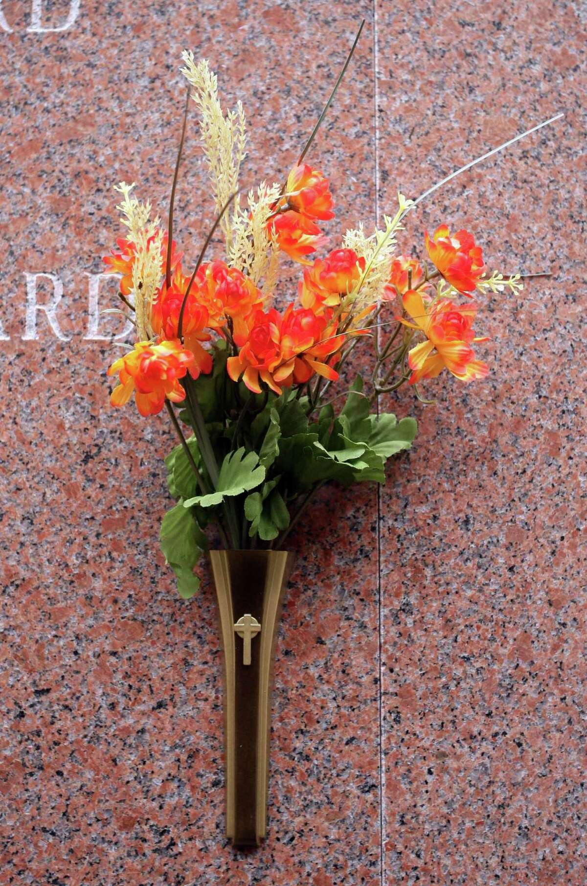 A plastic flower arrangement in the mausoleum at St. Lawrence Cemetery. The cemetery association leases the vase for one to seven years. Photo by Peter Casolino