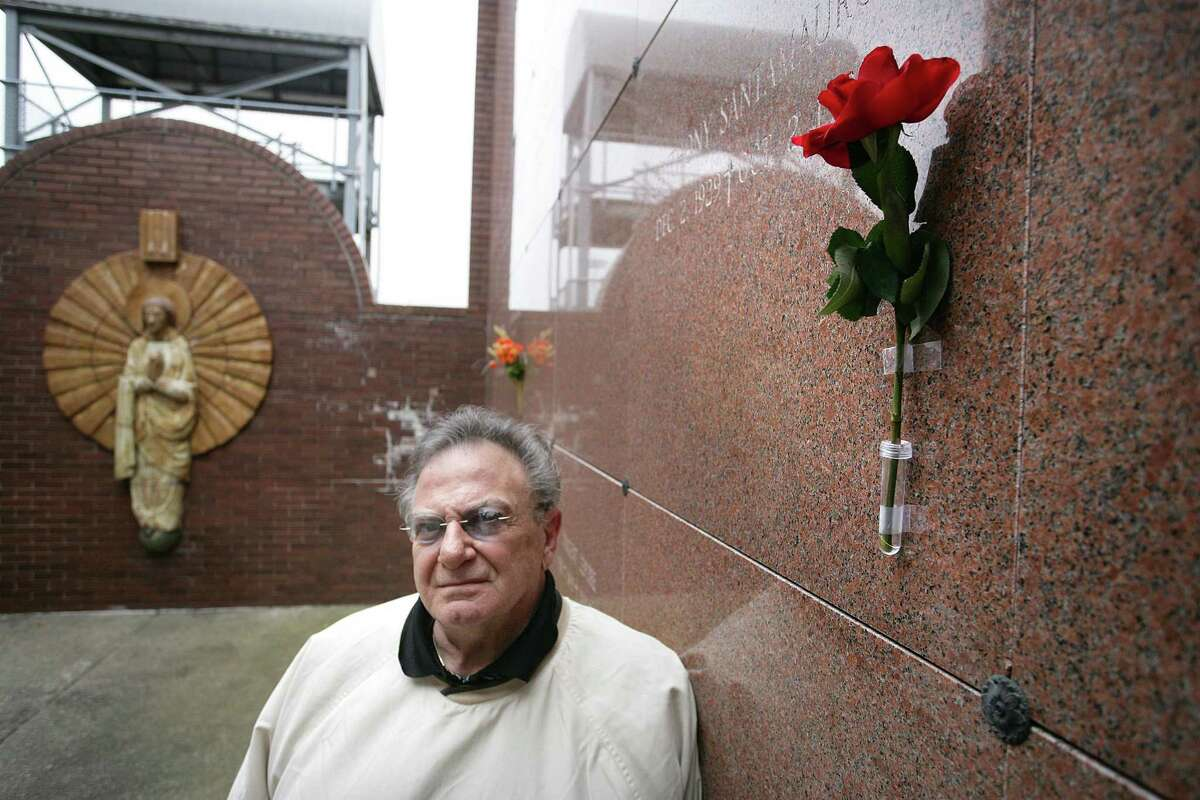 Tom Santamauro tapes a rose to the front of his brother Tony's crypt when he visits St. Lawrence Cemetery. It is then removed by staff. An approved leased vase is on a crypt behind him. Photo by Peter Casolino.