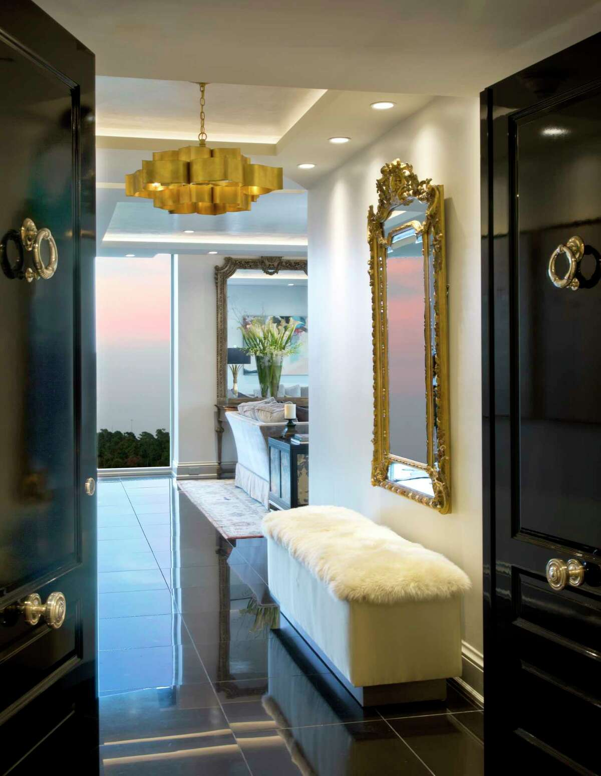 Glossy black doors open to a sophisticated foyer with a contemporary chandelier and sheepskin fur bench.