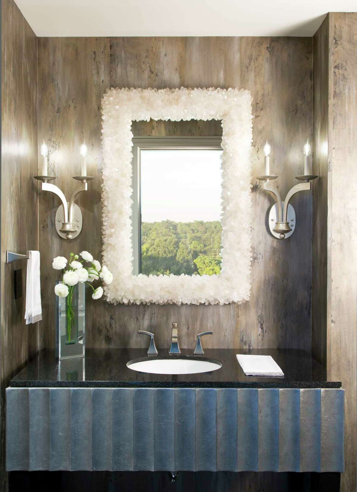 Hand-made, hand-painted wallpaper and a custom-made, quartz-encrusted mirror makes this just about the prettiest powder room in Houston.