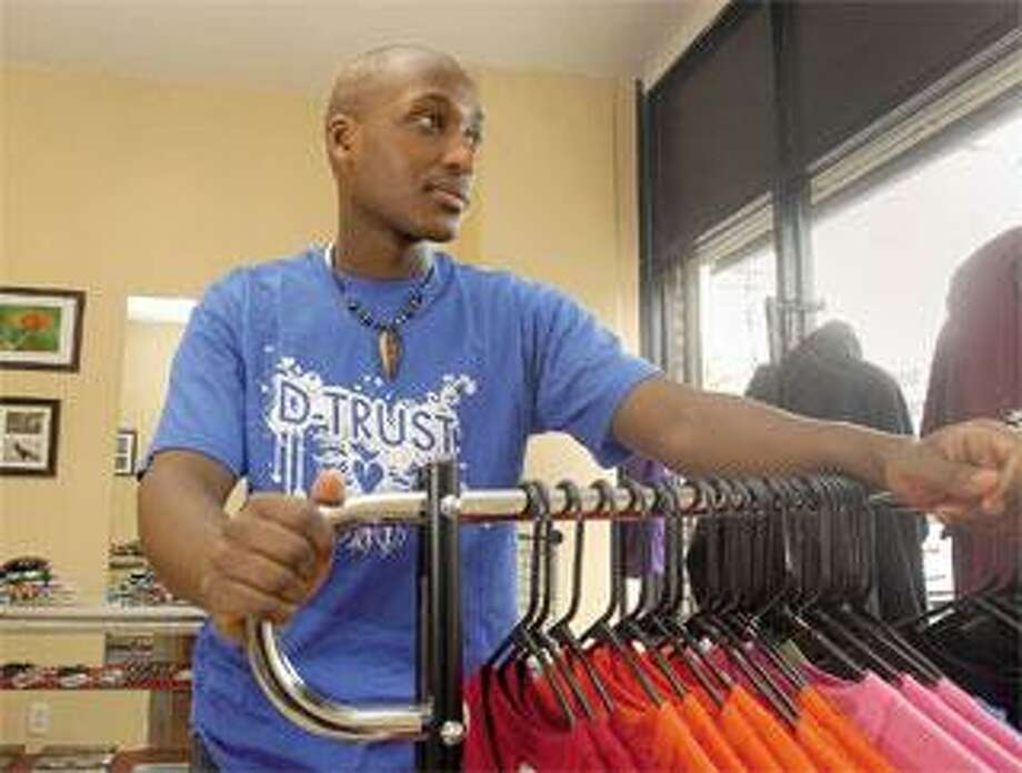 Daniel Ndamwizeye, a SCSU student and a survivor of the Rwandan genocide, displays some of the clothing for sale in his West Haven store. (Brad Horrigan/Register)