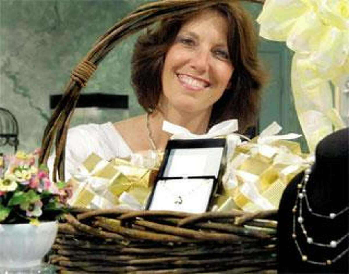 Jeannie DeSimone of Cellini Design Jewelers shows some of the boxed gifts that will be given to the first 100 people who come with proof of unemployment. (Melanie Stengel/Register)