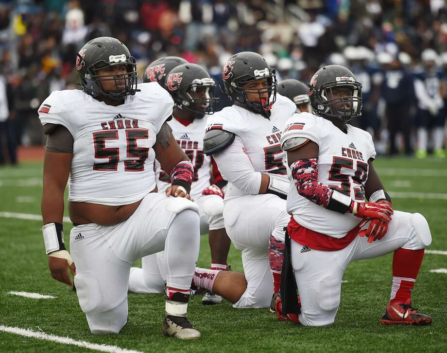 Wilbur Cross' Travis Jones (55, left) takes a knee with his teammates during the Elm City Bowl in 2016 (Photo Catherine Avalone / New Haven Register)