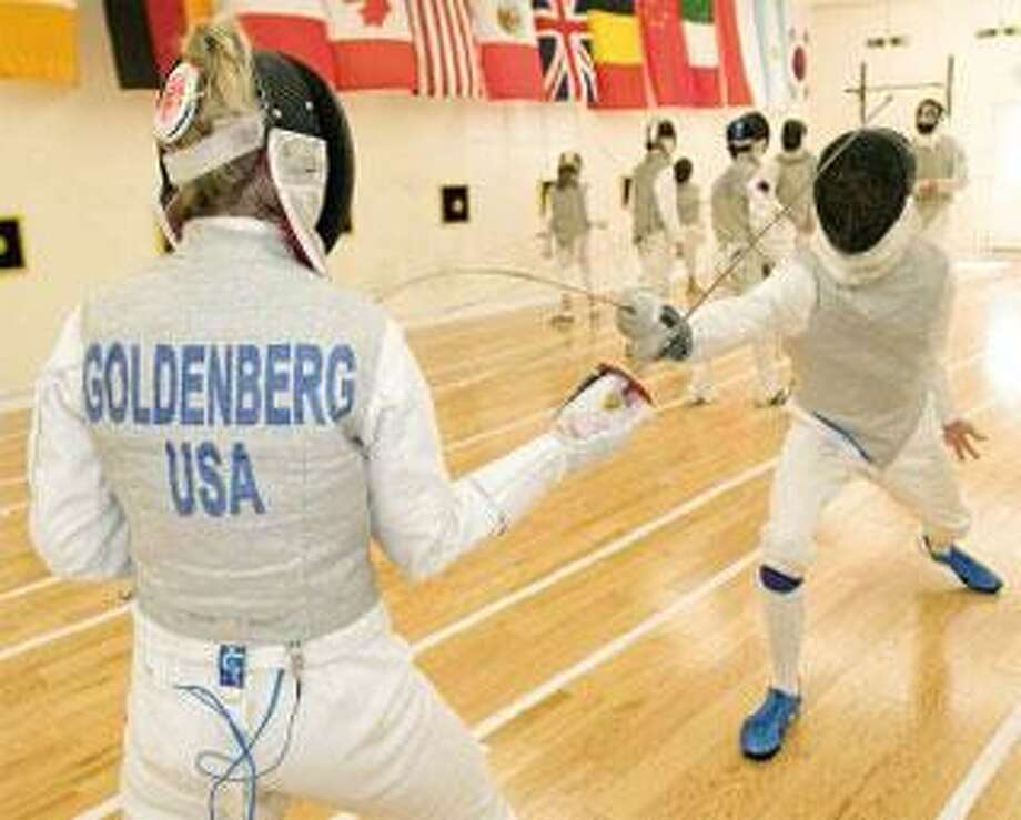 Daniela Goldenberg, a member of the Penn State team that won this year's NCAA fencing championship, practices with Andrew Simon, both of Guilford. (Thomas Cain/Register)