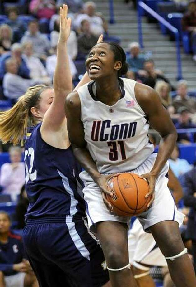 Connecticut's Tina Charles looks up toward the basket as Vanguard's Molly Pfohl guards her in the second half of an NCAA women's college exhibition basketball game in Hartford, Conn., Monday, Nov. 9, 2009. UConn defeated Vanguard 98-68.  (AP Photo/Bob Child) Photo: AP / FR170410 AP