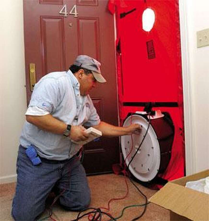 Robert Matto, owner of RPM Energy Solutions, conducts a blower door test to find air leaks at Hillcrest, an elderly housing complex in South Windsor. (Brad Horrigan/Register)