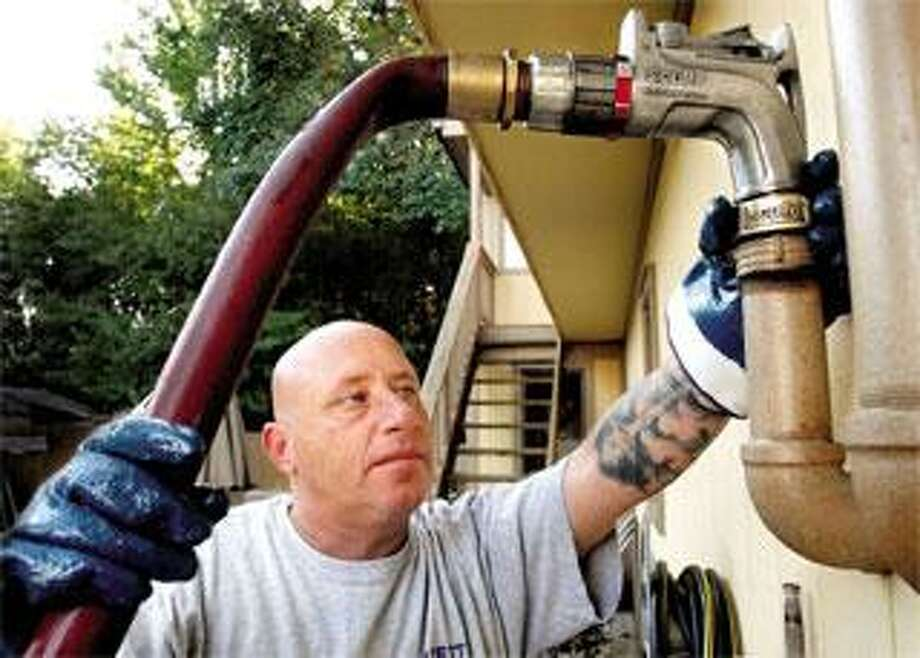 Nicholas Libretti, owner of Libretti & Son Fuel in East Haven, fills the oil tank at a home in East Haven. (Melanie Stengel/Register photos)