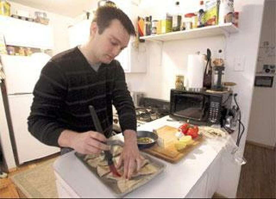 Andrew Lisy prepares pita wedges while making baba ghanouj in his apartment in Manhattan's Financial District in New York. Lisy, 24, lost his Wall Street job two months ago and has been immersing himself in new hobbies, including becoming a better cook. (Associated Press photos)