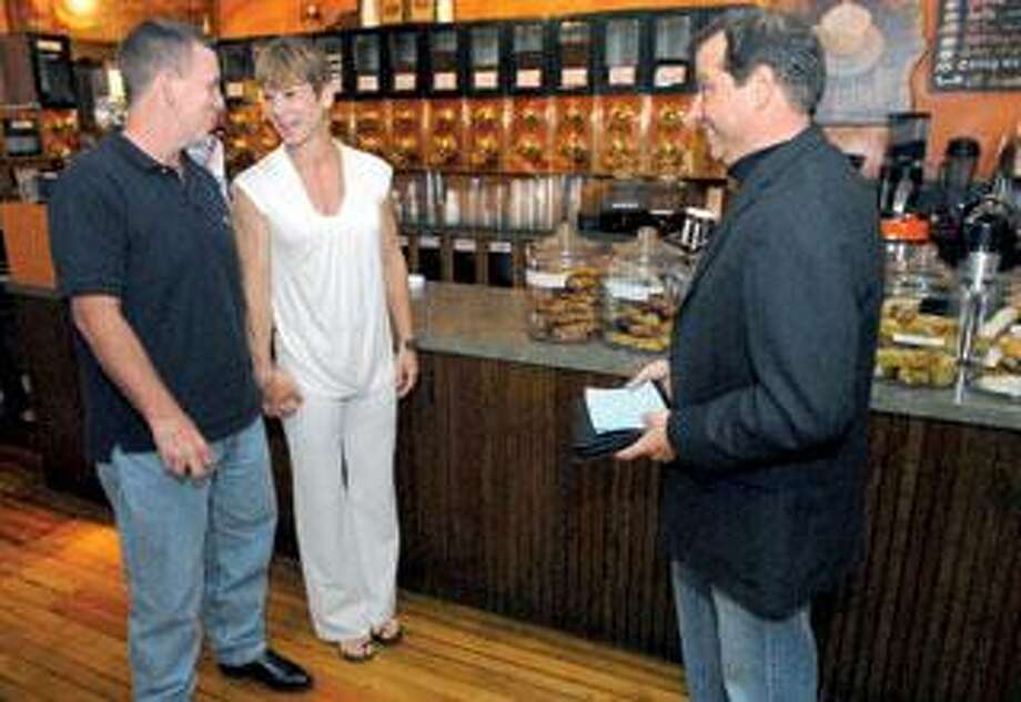 Frank Regan of Branford, left, and Theresa Sansone of New Britain are married Friday by Justice of the Peace Don Gentile at the Common Grounds coffee shop in Branford. (Mara Lavitt/Register)