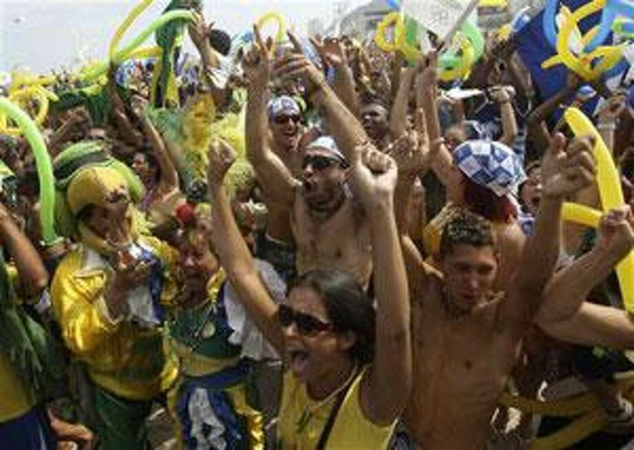 People celebrate after Rio de Janeiro won the nomination to host the 2016 Olympic Games at the Copacabana beach, in Rio de Janeiro, Friday, Oct.2, 2009. (AP Photo/Silvia Izquierdo)
