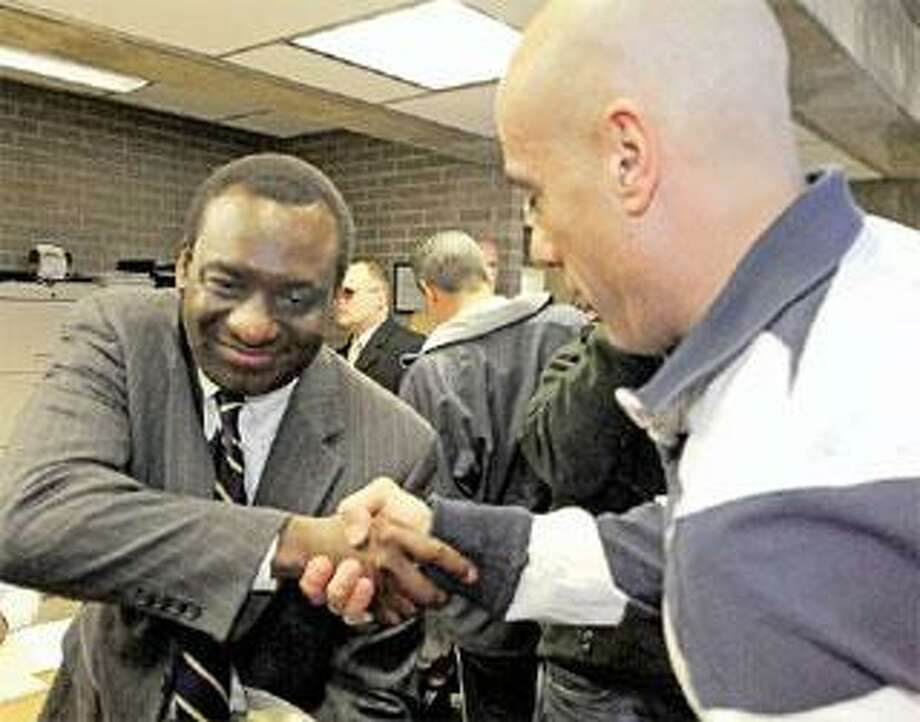 City Corporation Counsel Victor Bolden, left, congratulates Firefighter Mark Vendetto on his promotion to lieutenant Tuesday. The Board of Fire Commissioners elevated 14 of the 20 city firefighters involved in the Ricci v. DeStefano reverse discrimination lawsuit. (Peter Hvizdak/Register)