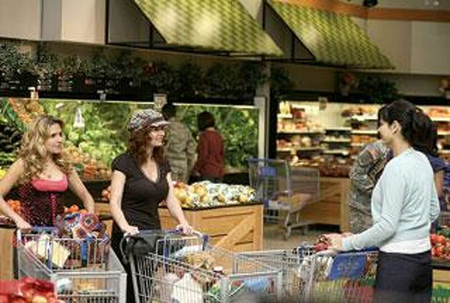 "Two ""Army Wives,"" played by Sally Pressman, left, and Brigid Brannagh, share an awkward moment with an ostracized Denise (Catherine Bell) in the season's second episode. (Lifetime Photos)"