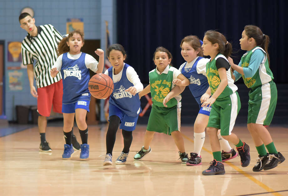 Giselle O'Bryant is followed by her team members as she dribbles the ball down the court on Tuesday afternoon as Santo Nino's Shiloh Ferral and her teammates chase after O'Bryant at Tarvar Elementary during a Boys and Girls Club League basketball game. Photo: Danny Zaragoza
