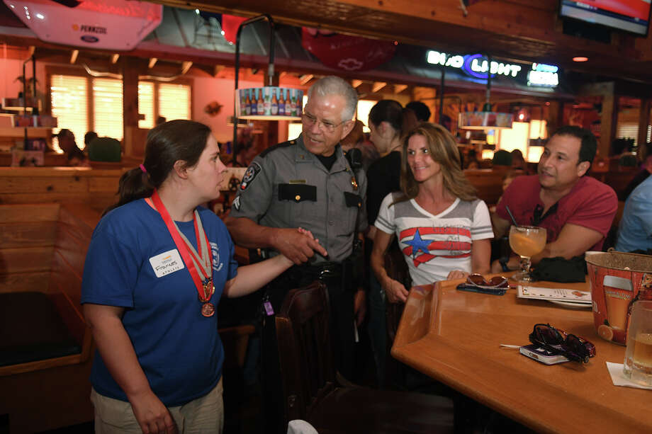 Gene Barnett, center, from Precinct 4 Constable's Office, introduces Special Athlete Frances, left, to Dody and Ricky Pedraza, right, of Kingwood, whose son Jake is on the Special Olympics swim team, during the Tip-A-Cop event at Texas Roadhouse in Kingwood on July 27, 2017. (Photo by Jerry Baker/Freelance) Photo: Jerry Baker, Freelance / Freelance