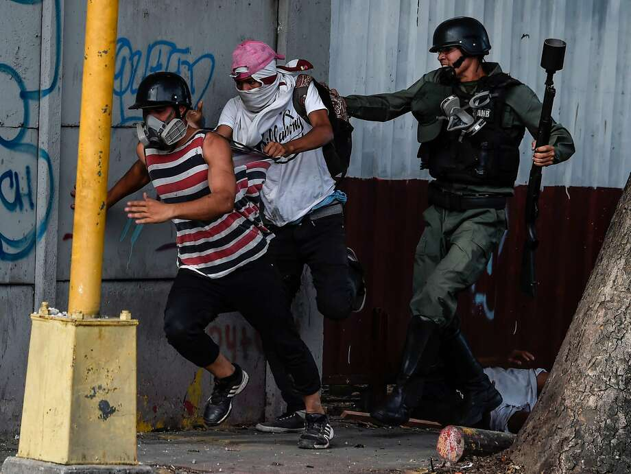 A National Guard member grabs an anti gov ern ment activist during sporadic clashes in Caracas. Photo: JUAN BARRETO, AFP/Getty Images