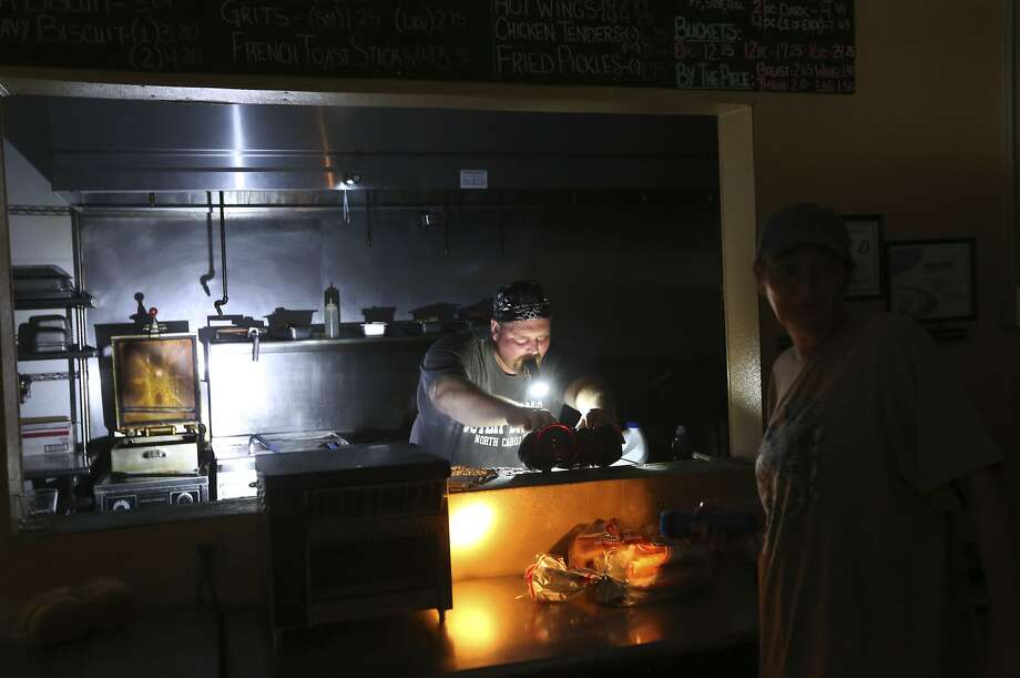 Aaron Howe cooks with a flashlight in his mouth at the Island Convenience store in Rodanthe on Hatteras Island. An estimated 10,000 tourists were told to evacuate the region Friday. Photo: Steve Earley, Associated Press