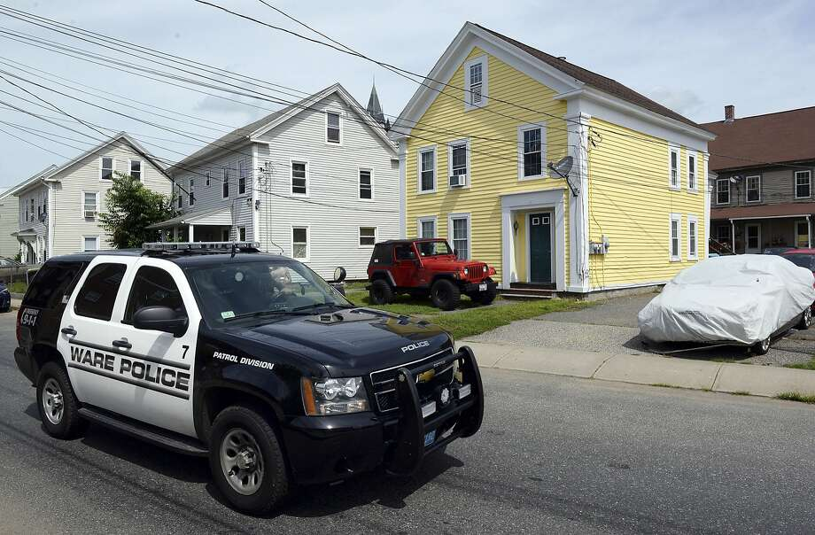 A police vehicle in Ware, Mass., passes the yellow house where Paul Shanley will live. Shanley was convicted of raping a boy. Photo: Dave Roback, Associated Press