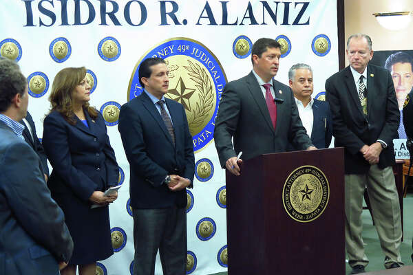 """Webb/Zapata County District Attorney Isidro """"Chilo"""" Alaniz, at podium, was accompanied by law enforcement representatives and customs brokers Tuesday morning at the Webb County Justice Center for a press conference to caution paisanos of fraudulent scams regarding the nationalization process of importing their vehicles."""