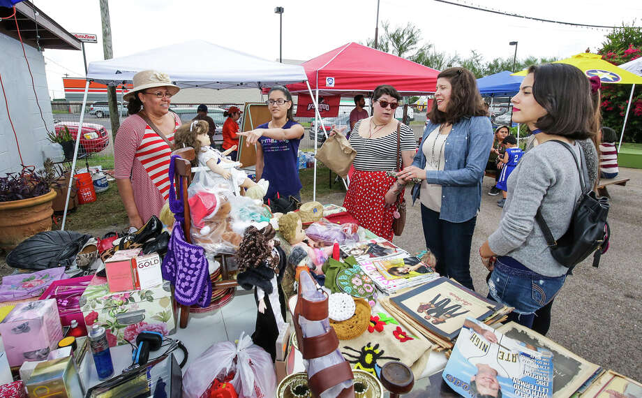 Lina Rodriguez, left, tends to customers at her vendor booth Saturday morning during the Avenida San Bernardo Midtown Block Party at Pan American Courts. Photo: Victor Strife/Laredo Morning Times