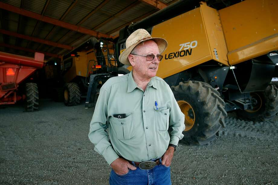 Rice farmer Michael Rue stands with grain combines that sit idle until the autumn harvest gets under way at his Rue and Forsman Ranch in Yuba County. Photo: Paul Chinn, The Chronicle
