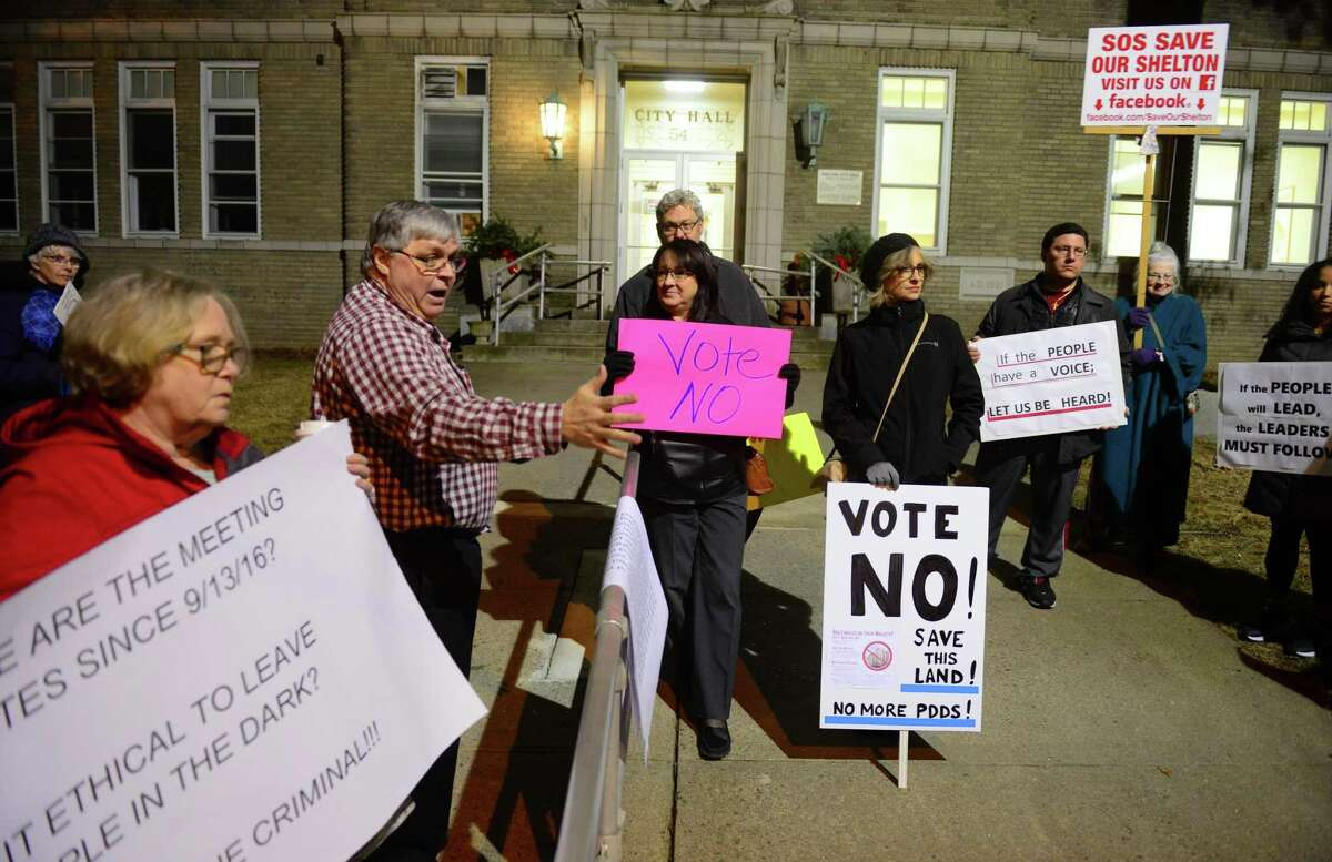 Save Our Shelton, led by Greg Tetro, arm raised, leads a protest against the development of Shelter Ridge land before the start of the Shelton Planning and Zoning Commission meeting at City Hall in Shelton, Conn., on Thursday Jan. 20, 2017. Developers want to pave over 125 acres of wooded land that contains a historic hiking trail, is a natural wildlife habitat and contains wetlands with the Far Mill River running along one side.