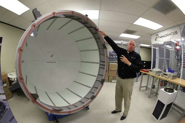 NanoRacks project manager Brock Howe uses a  full-scale model to demonstrate how a commercial airlock system will work.