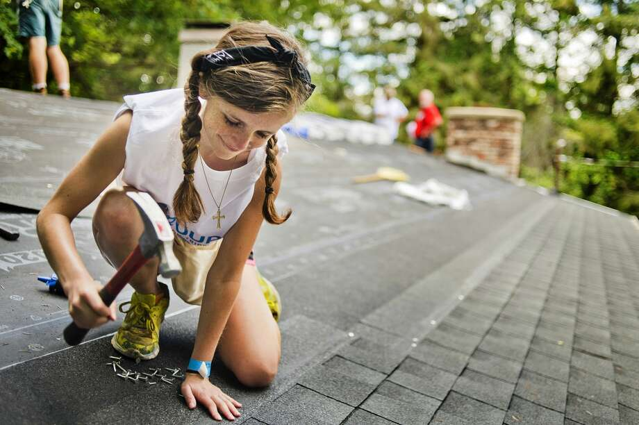 Riley Mathers of Virginia works to retile the roof of Ruth Laatsch at E. David Road on Monday, July 24, 2017 as part of the Call to the Creek group work project, which brings hundreds of high school and college students from around the country to do volunteer work in the Midland area. Photo: (Katy Kildee/kkildee@mdn.net)
