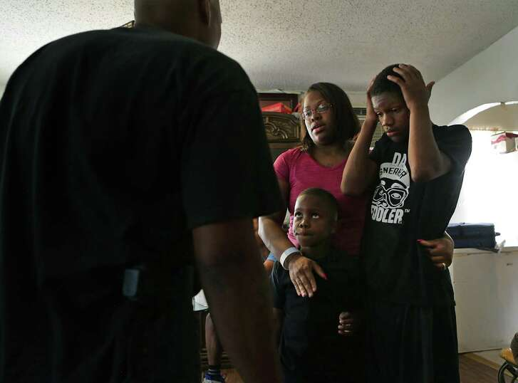 Cyntwanisha Whitley, center, mother of four year-old De'Earlvion Whitley who was killed in a drive by shooting, holds on to her sons Devin Brown, 12, right, and Corey Lewis, 7, as a friend of the family talks to her offering support, on Thursday, July 20, 2017.