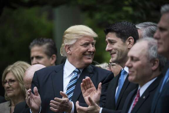 President Donald Trump claps with House Speaker Paul Ryan, R-Wis., and other House members after passage of a health-care bill in May. The debate on Trump offers insight on how ancient Romans defined legal arguments.