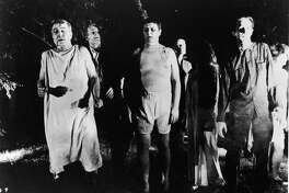 A line of undead 'zombies' walk through a field in the night in a still from the film, 'Night Of The Living Dead,' directed by George Romero, 1968. The movie is awash in useful metaphors.