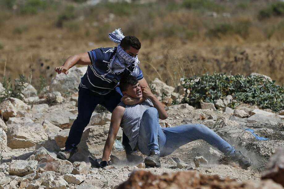 An undercover Israeli security officer detains a Palestinian protester near Ramallah on the West Bank. Photo: ABBAS MOMANI, AFP/Getty Images