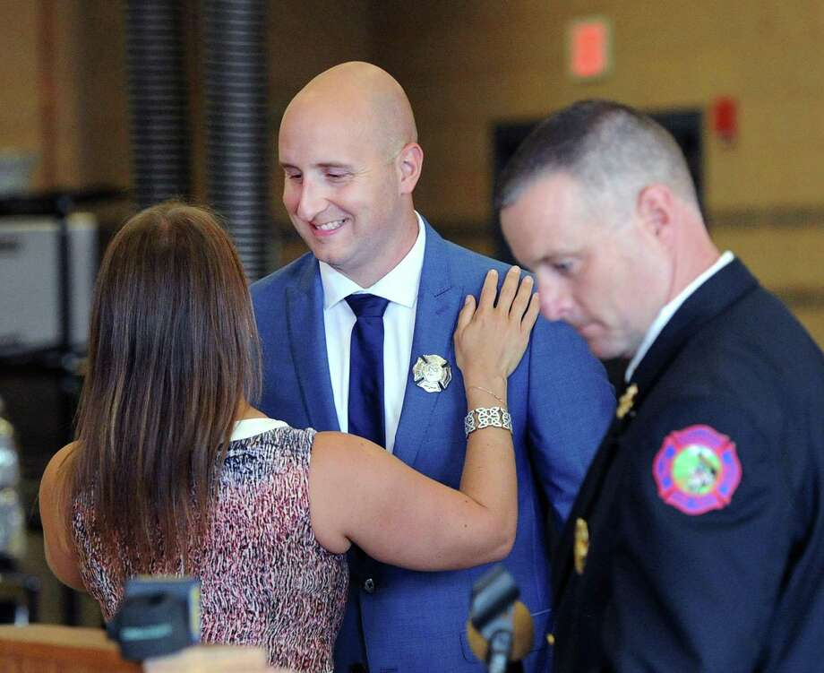 Newly sworn-in Greenwich Firefighter Peter Purcell, center, smiles after his wife Loriane, left, pinned his firefighter's badge on his jacket during the swearing in ceremony for five new Greenwich Firefighters, including Purcell, at Fire Department Headquarters in Greenwich, Conn., Friday morning, July 28, 2017. At right is Assistant Greenwich Fire Chief Robert Kick. Photo: Bob Luckey Jr. / Hearst Connecticut Media / Greenwich Time
