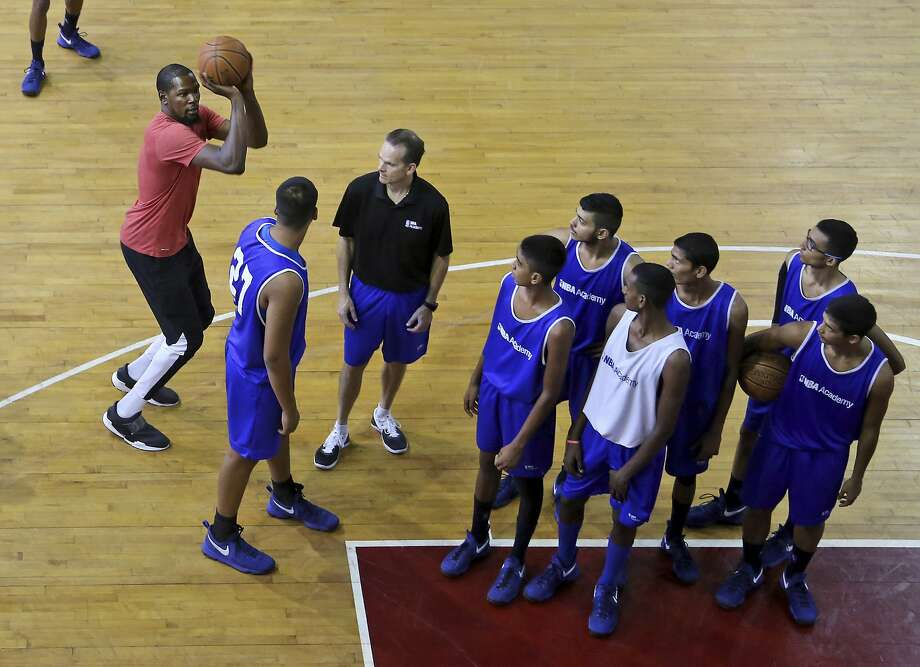 FILE – 2017 NBA Finals MVP Kevin Durant, left, of the Golden State Warriors displays a shooting technique during the tour of NBA Academy in Greater Noida near New Delhi, India in this Friday, July 28, 2017 file photo. Durant said he plans to return to India to run more basketball camps and meant no disrespect in his comments about the country. Photo: Altaf Qadri, Associated Press