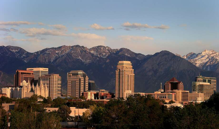 The Wasatch Range hovers over downtown Salt Lake City. Utah, like California, is suffering a housing crisis, with even fewer housing units per person than California. The problem is less acute because Utah has the largest families in the nation. Photo: Brant Ward, The Chronicle