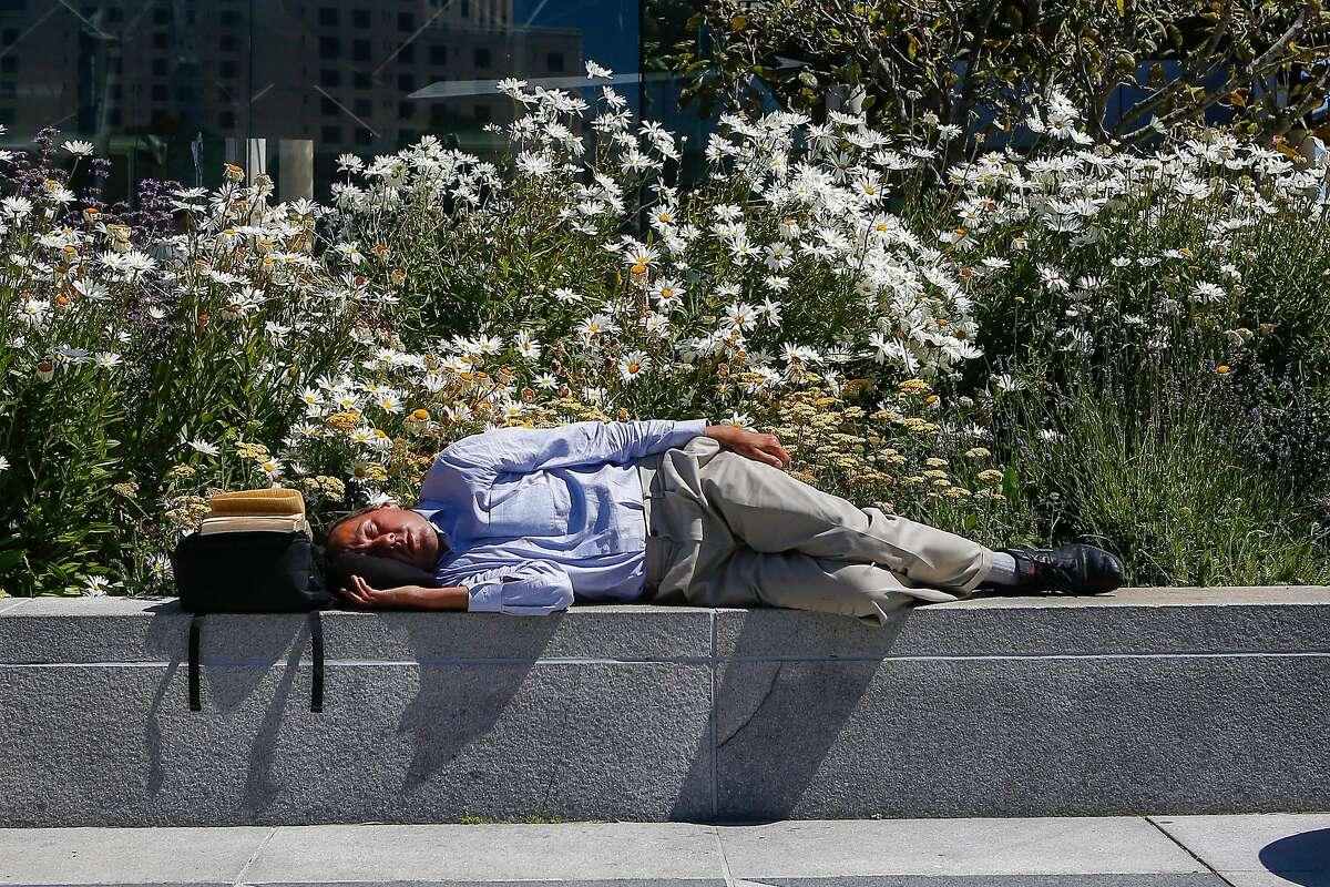 Michael Murawski naps in Yerba Buena Gardens in San Francisco on Friday, July 28, 2017.